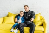 young father in police uniform watching tv with son while sitting on yellow couch at home