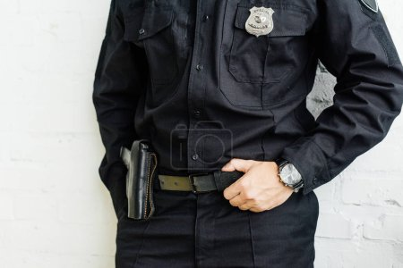 cropped shot of policeman standing in front of white brick wall