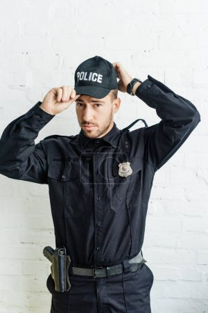 attractive young policeman putting on cap in front of white brick wall