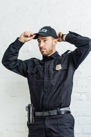 handsome young policeman putting on cap in front of white brick wall
