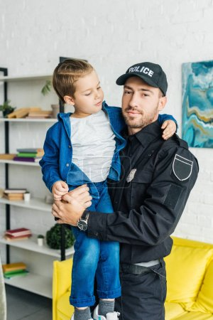 handsome young father in police uniform carrying his little son and looking at camera
