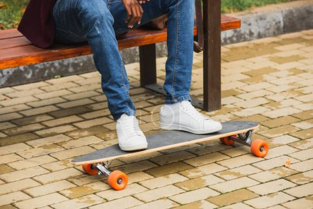 cropped shot of man with skateboard sitting on bench