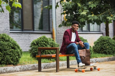 smiling young man with leather backpack and skateboard sitting on bench on street