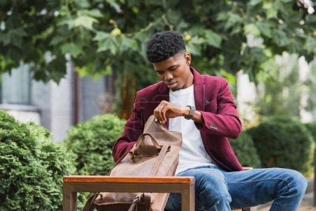 Photo pour Etudiante sérieuse ouvrant cuir sac à dos en position assise sur le banc sur la rue - image libre de droit