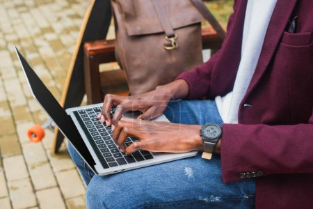 cropped shot of african american freelancer using laptop on bench with leather backpack and skateboard