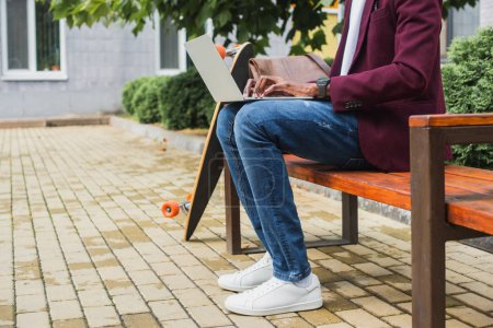 cropped shot of freelancer using laptop on bench with skateboard