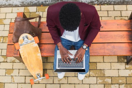 top view of young freelancer using laptop on bench with leather backpack and skateboard
