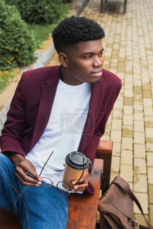 handsome young man with paper cup of coffee and eyeglasses sitting on bench