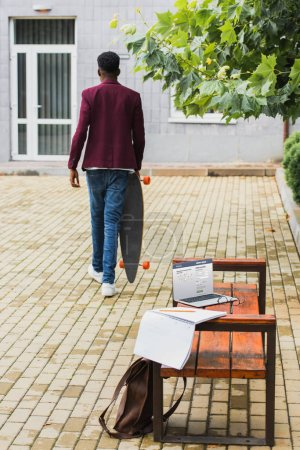 rear view of freelancer walking with skateboard on street with laptop with facebook website on screen lying on bench on foreground