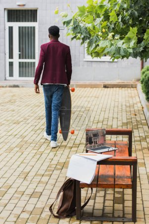 back view of man walking with skateboard on street with laptop with online booking website on screen on foreground