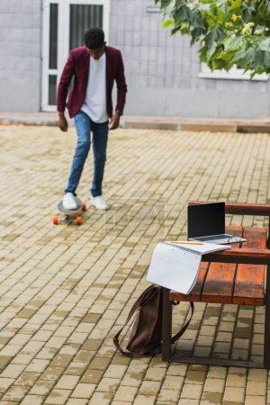 hombre joven en la calle con portátiles en Banco en primer plano