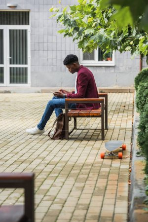Photo for Stylish young student using smartphone while sitting on bench - Royalty Free Image