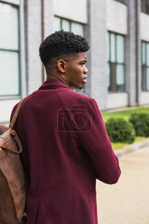handsome young student with leather backpack walking by street