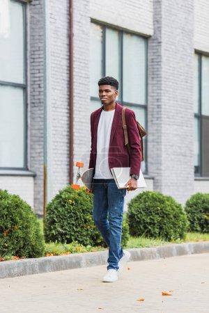 Photo pour Beau jeune étudiant avec sac à dos et skateboard à pied par la rue - image libre de droit