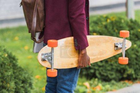 Photo pour Recadrée tir d'étudiant avec sac à dos et skateboard à pied par la rue - image libre de droit