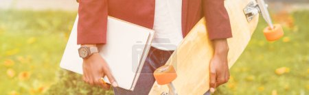 cropped wide shot of stylish student with notebooks and skateboard standing on street