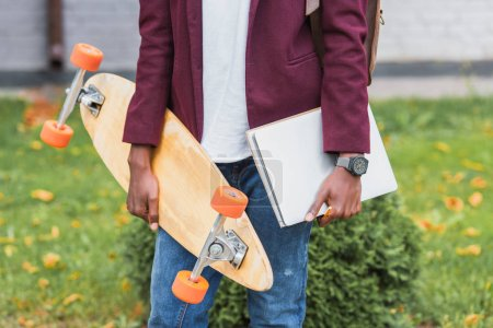 cropped shot of stylish student with notebooks and skateboard standing on street