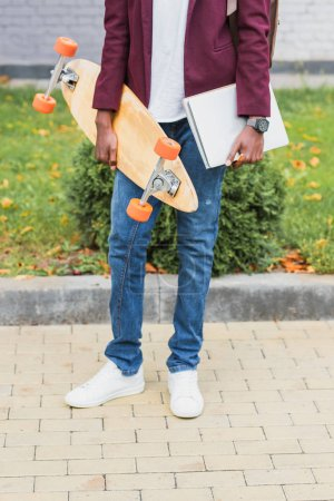 cropped shot of student with notebooks and skateboard standing on street