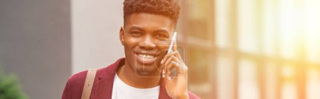wide toned shot of smiling young man talking by phone and looking at camera on street