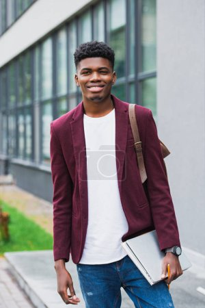 Photo for Happy young student with backpack and notebooks looking at camera on street - Royalty Free Image
