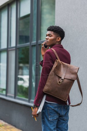 handsome young student with leather backpack talking by phone on street