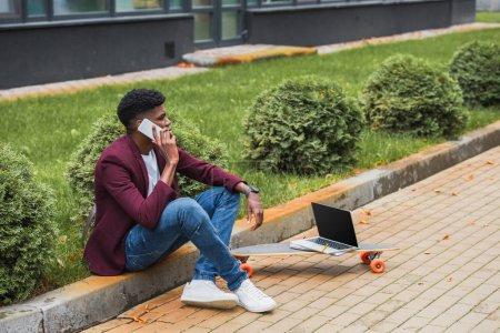 african american freelancer sitting on curb on street near laptop on skateboard