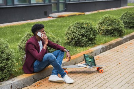 young freelancer talking by phone while sitting on curb on street with laptop with sportsbet website on screen lying on skateboard