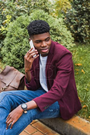 smiling young man talking by phone while sitting on curb on street