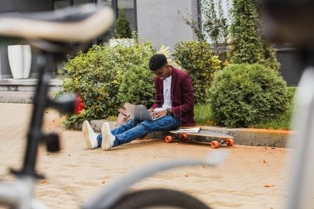 young student using laptop and writing in notebook while sitting on curb on street