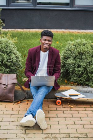 happy young student using laptop while sitting on curb on street and looking at camera