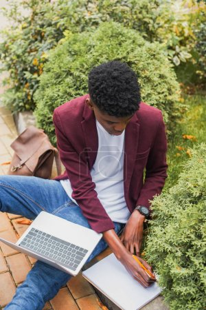 high angle view of young freelancer using laptop and writing in notebook while sitting on curb on street