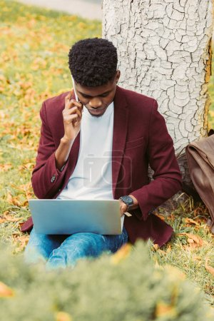 african american teleworker using laptop and talking on smartphone in park