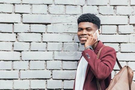 cheerful african american man talking on smartphone near white brick wall