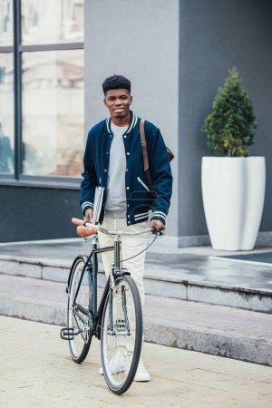 Photo for Handsome african american freelancer with documents and bicycle - Royalty Free Image