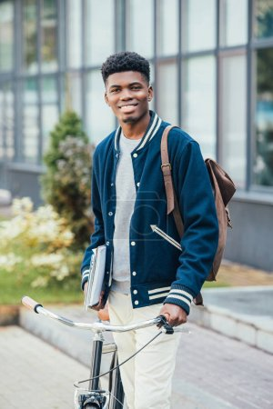 Photo pour Beau Afro-Américain joyeux avec des documents et vélo dans la rue - image libre de droit