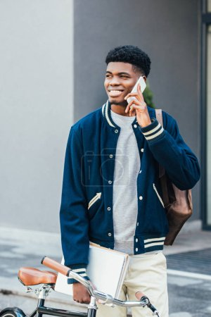 handsome smiling african american man with documents talking on smartphone near bike