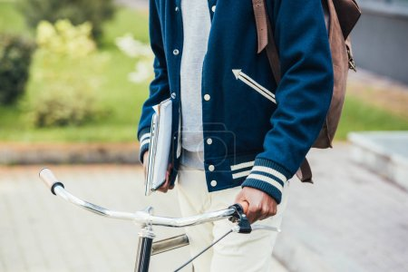 cropped view of male student with papers laptop and bicycle on street