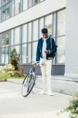 """Постер, картина, фотообои """"афро-американских дистанционный работник с документами с помощью смартфона и стоя на велосипедов"""""""