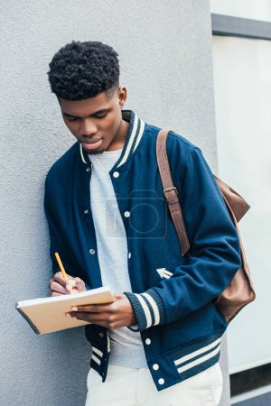 stylish focused african american student writing in textbook