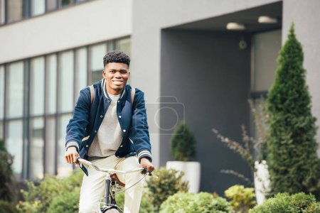 Photo for African american smiling man riding bicycle in city - Royalty Free Image