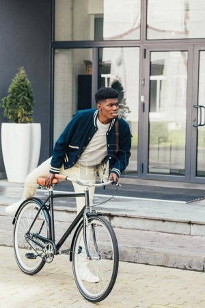 stylish african american man riding bicycle in city