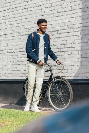 african american man standing with bicycle near white brick wall