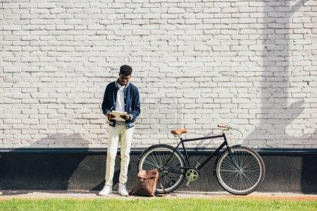Photo pour Afro-américaine pigiste lire les documents et debout près de vélo au mur de briques blanches - image libre de droit