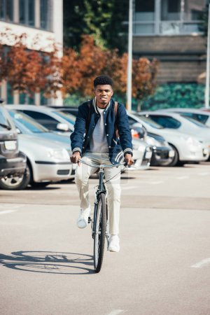handsome african american man riding trendy bike in city
