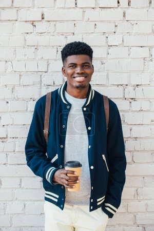 cheerful african american man holding coffee to go near white brick wall