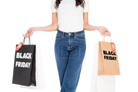 cropped view of girl holding shopping bags with black friday sale signs isolated on white