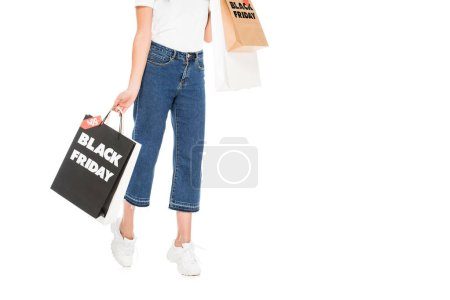 cropped view of shopaholic holding shopping bags with black friday sale signs isolated on white