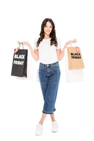 attractive girl posing with shopping bags with black friday sale signs isolated on white