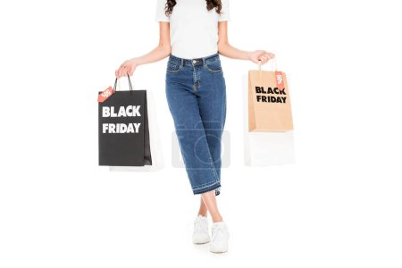 cropped view of stylish shopper holding shopping bags with black friday sale signs isolated on white