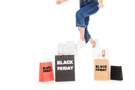 cropped view of girl jumping near shopping bags with black friday sale signs isolated on white